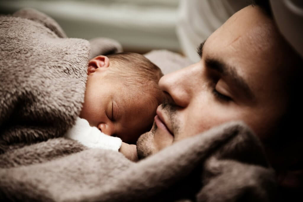 A man is sleeping with a baby, love as a source of motivation.
