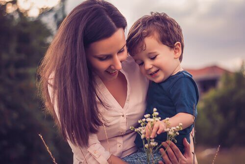 a woman and her son happily looking at a flower