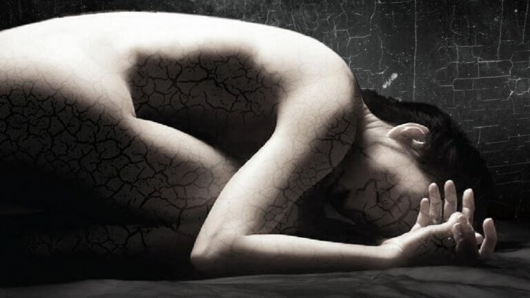a woman with fragmented skin crumpled on the ground