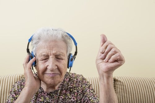 An elderly woman is listening to music.