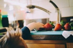 boy grabbing strawberry