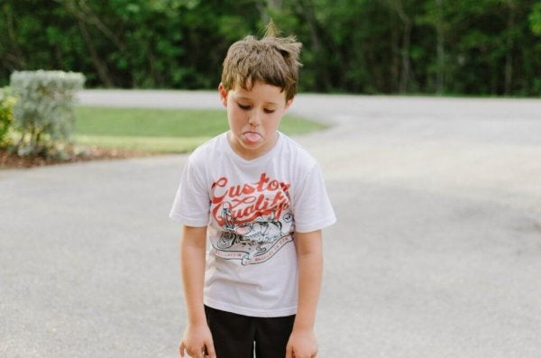 Boy sticking out tongue and throwing a tantrum.