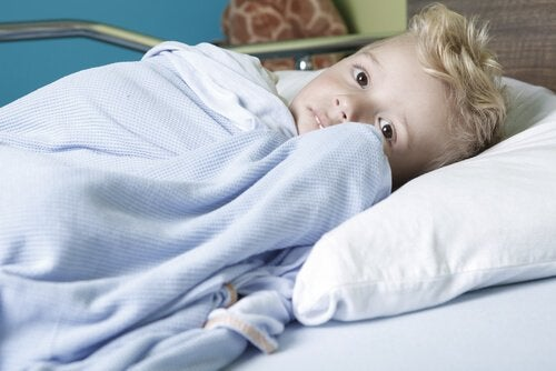 A boy with cancer is in a hospital bed.