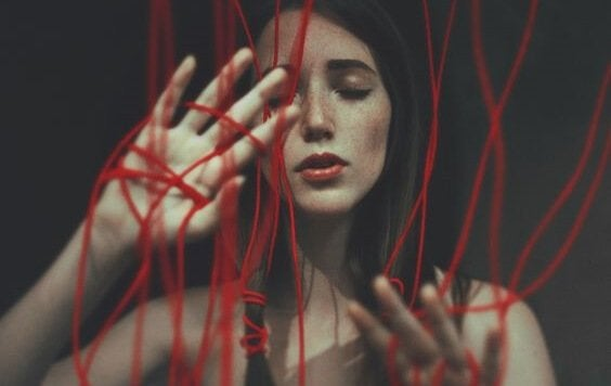 A woman tangled in red cords.