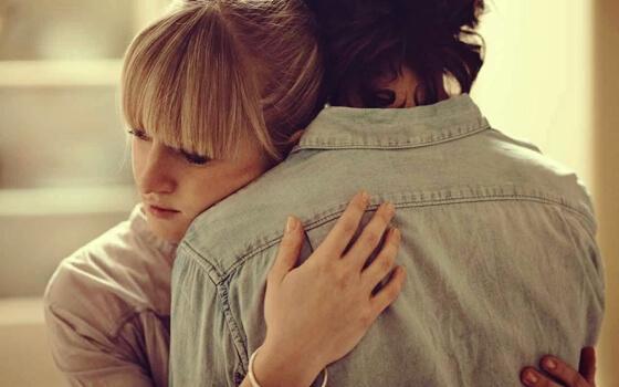 A sad couple hugging.