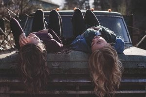 A true friendship: two friends laying on a truck.