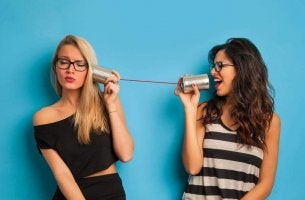 Two girls are gossiping into a can phone.