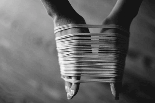 Hands bound with strings.