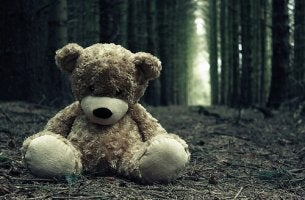 A teddy bear is sitting on the ground in the woods.