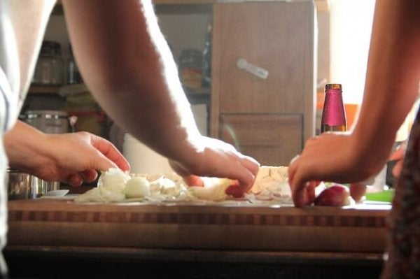 Cooking together, chopping onions.