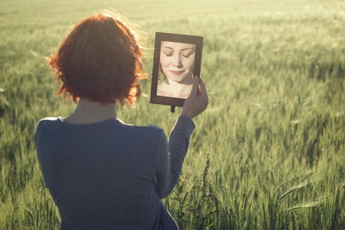 Woman in a field looking in a mirror.