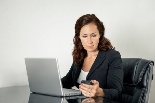 A woman at a desk with a laptop and cell phone.