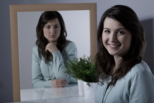 A woman with cyclothymic disorder at the mirror, happy and sad.
