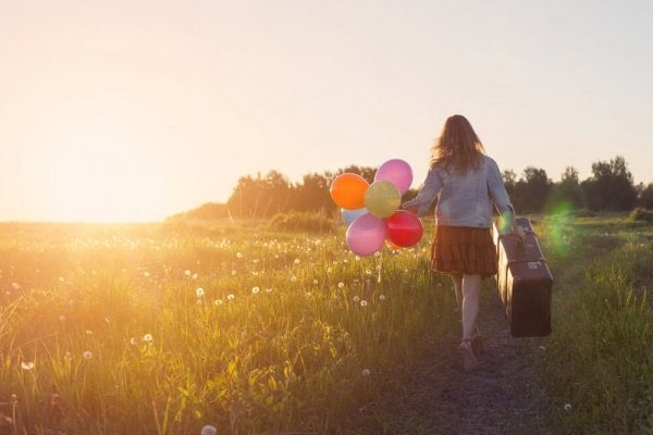 Woman with case and balloons