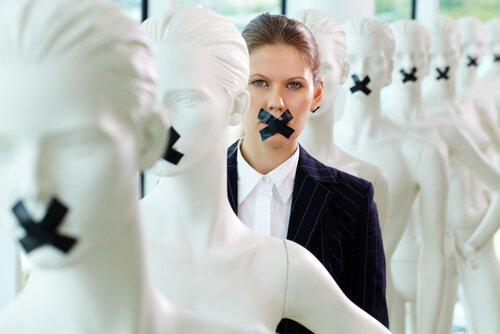 A woman silenced with tape over her mouth along with mannequins.
