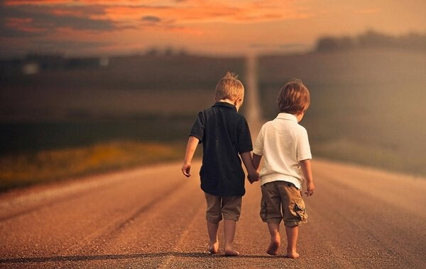 Types of friends: two boys walking down a road holding hands.