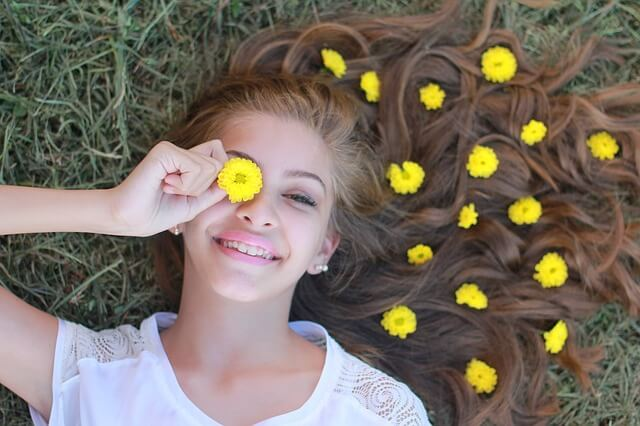 A female teenager has a flower over her eye.