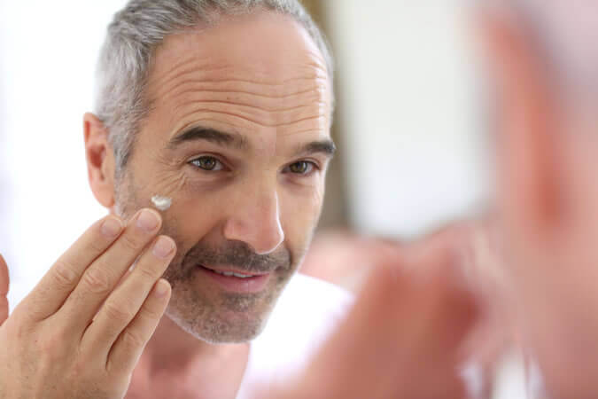A man applying eye cream.