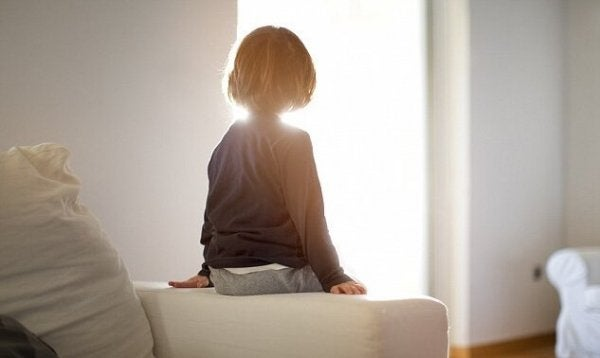 child with reactive attachment disorder sitting alone on the couch