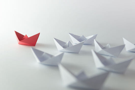 red paper boat symbolizing leadership as a social identity