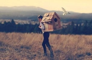 A man carrying a large birdhouse.
