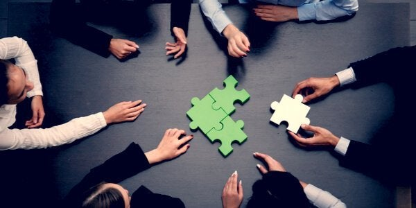 Business people with jigsaw