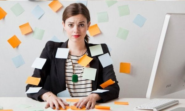 Overworked woman with post-it's stuck to her.