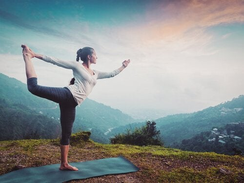 A woman doing yoga outdoors.