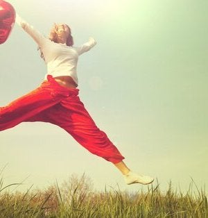 Woman jumping with red balloon