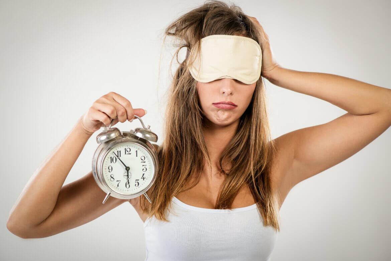 woman with alarm clock representing circadian rhythm sleep disorder