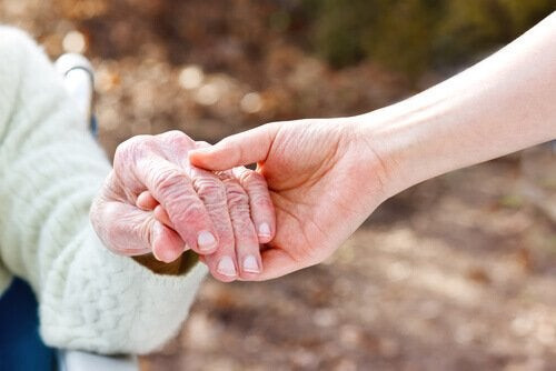 someone holding the hand of a person with Alzheimer's