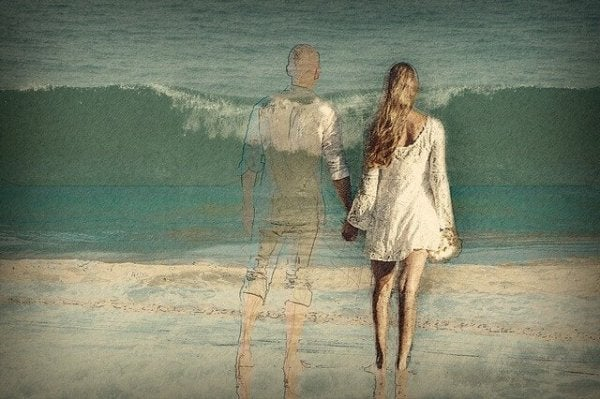 A couple on the beach, the man transparent like a ghost.