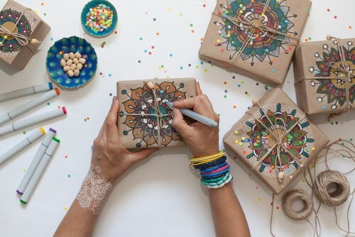 girl drawing mandalas onto wrapped gifts