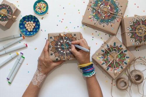 girl drawing mandalas onto wrapped gifts