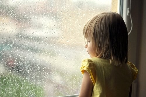 girl looking out the window as a symbol of emotional wounds from the past