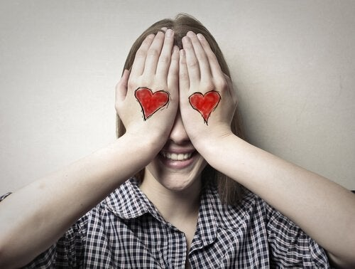 woman covering her eyes with her hands (which have hearts on them) symbolizing blind love