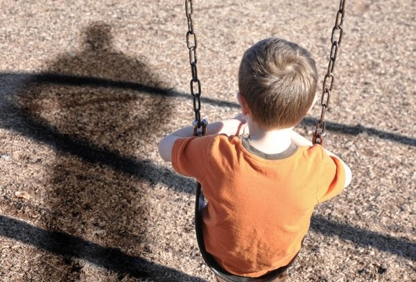 sad boy sitting on swing because of emotional neglect at home