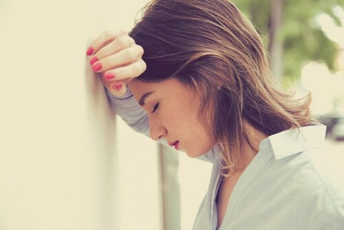 woman dealing with emotional exhaustion leaning her head against the wall