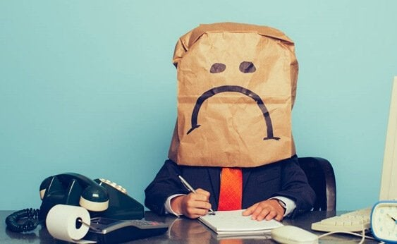 A man at work with a sad face bag over his face.