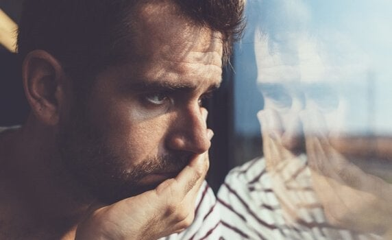 sad man going through the stages of grief looking out the window