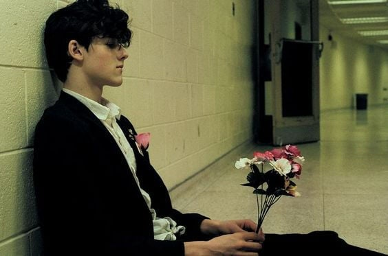 boy sitting in hallway with flowers symbolizing wanting to leave your partner but not being able to