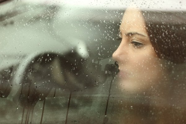 woman looking out of car window using emotional reasoning to think about someone far away