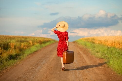 woman with wanderlust syndrome walking down a path with her suitcase