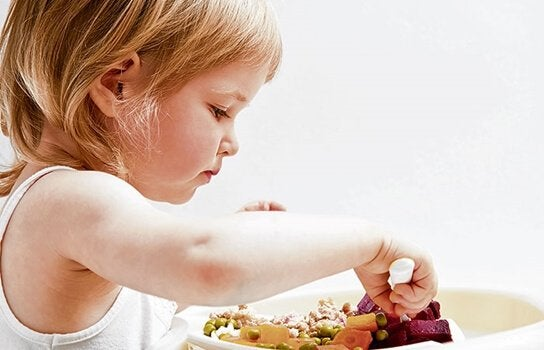 Girl eating vegetables independently