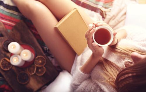 woman reading a book while drinking tea