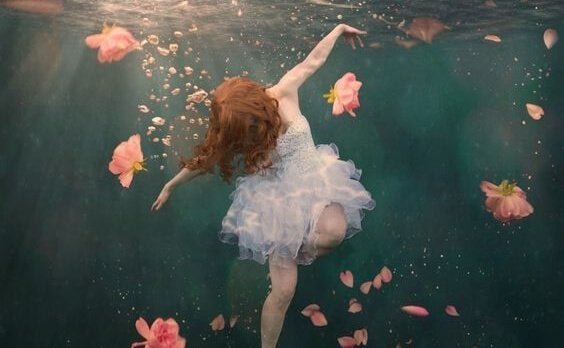 Woman in dress floating underwater surrounded by flowers.