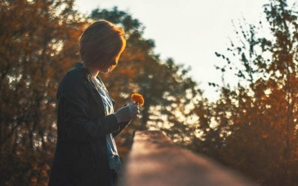 woman looking at flower and remembering memories