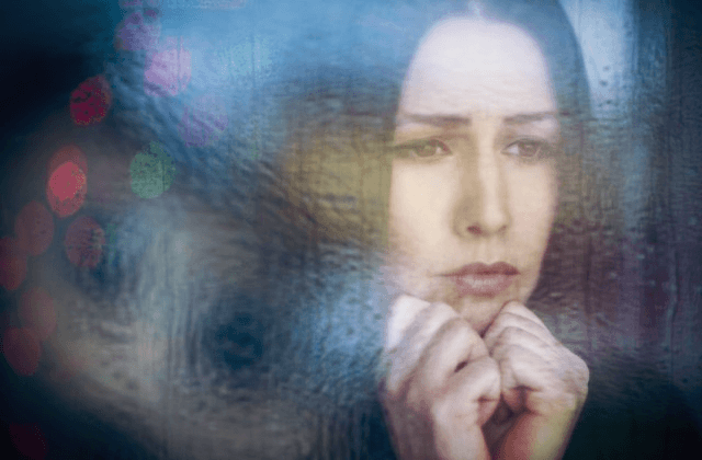 depressed woman looking through window
