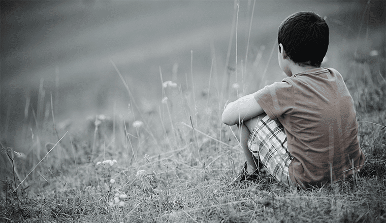 A traumatized child sitting in a field.