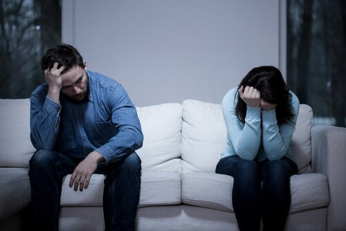 Angry couple with negative attitude sitting on couch.